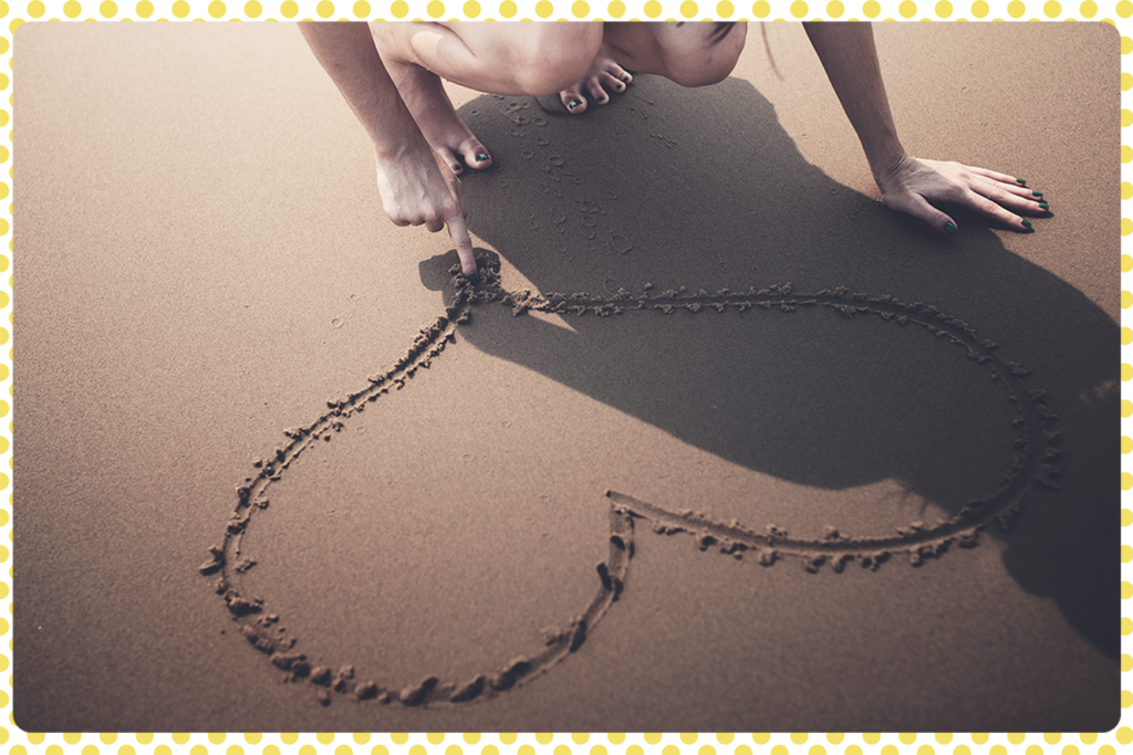 Être belle au naturel, c'est avant tout être bien dans sa peau. Photo représentant le dessin d'un cœur sur le sable symbole du bien-être comme ingrédient essentiel de beauté.